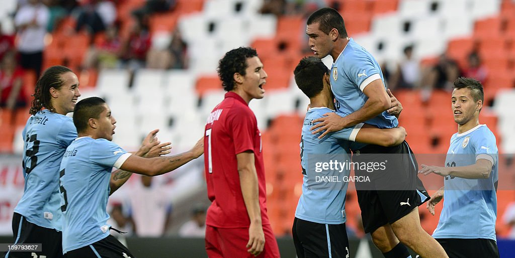 Uruguay's defender Fabricio Formiliano (2-R) celebrates with teammates after scoring a goal against Peru during their South American U-20 final round football match at Malvinas Argentinas stadium in Mendoza, Argentina, on January 20, 2013. Four teams will qualify for the FIFA U-20 World Cup Turkey 2013. AFP PHOTO / DANIEL GARCIA