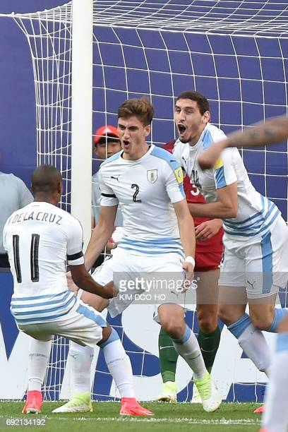 Uruguay's defender Santiago Bueno celebrates with teammates Nicolas De La Cruz and Agustin Rogel after scoring during their U20 World Cup...