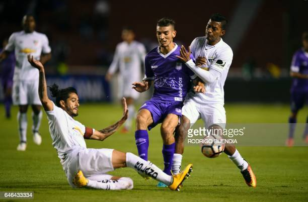 Uruguay's Defensor Sporting Martin Rabunal vies for the ball with Ecuador's Liga de Quito Norberto Araujo and John Narvaez during their Copa...