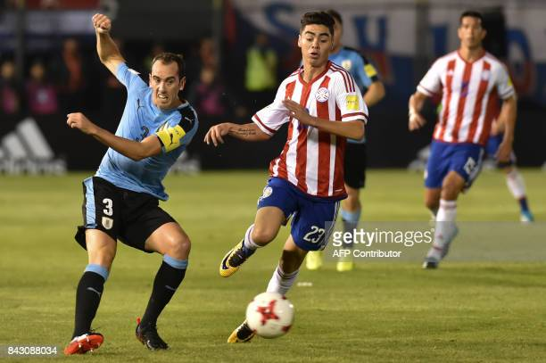 Uruguay's Diego Godin strikes the ball as Paraguay's Miguel Almiron looks on during their 2018 World Cup qualifier football match in Asuncion on...