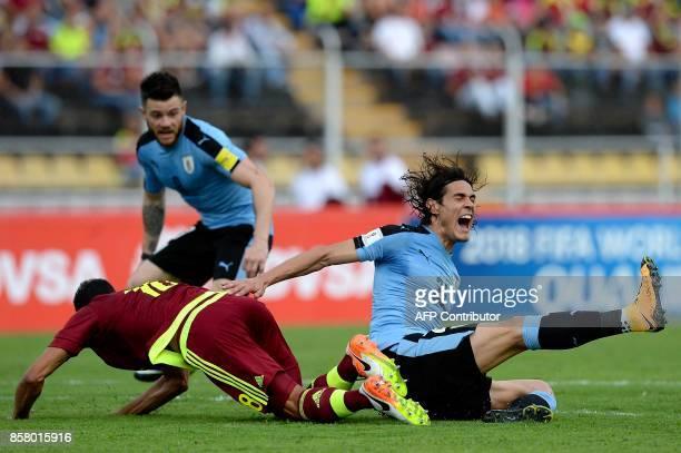 Uruguay's Edinson Cavani and Venezuela's Victor Garcia fall down during their 2018 World Cup qualifier football match in San Cristobal Venezuela on...