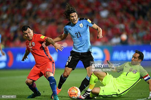 TOPSHOT Uruguay's Edinson Cavani Chile's Gary Medel and Chile's goalkeeper Claudio Bravo vie for the ball during their 2018 FIFA World Cup qualifier...