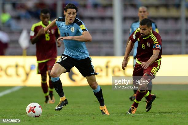 Uruguay's Edinson Cavani drives the ball past Venezuela's Tomas Rincon during their 2018 World Cup qualifier football match in San Cristobal...