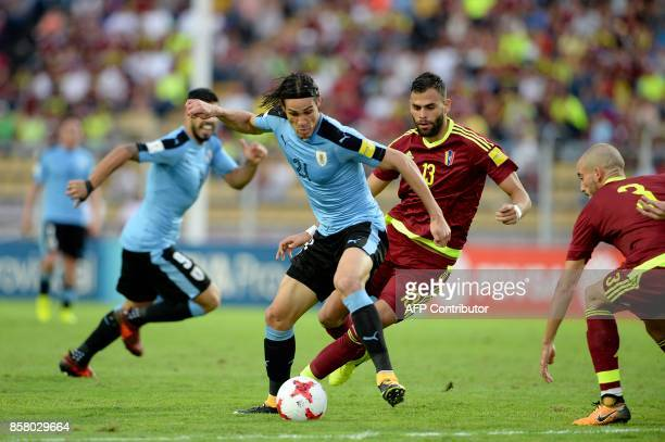 Uruguay's Edinson Cavani is marked by Venezuela's Jhon Chancellor and Mikel Villanueva during their 2018 World Cup football qualifier match in San...