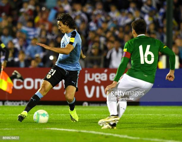Uruguay's Edinson Cavani runs with the ball pressured by Bolivia's Ronald Raldes during their 2018 World Cup football qualifier match in Montevideo...