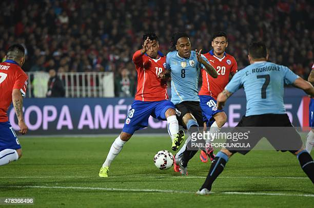 Uruguay's forward Abel Hernandez vies for the ball with Chile's defender Gonzalo Jara and Chile's midfielder Charles Aranguiz next to Uruguay's...