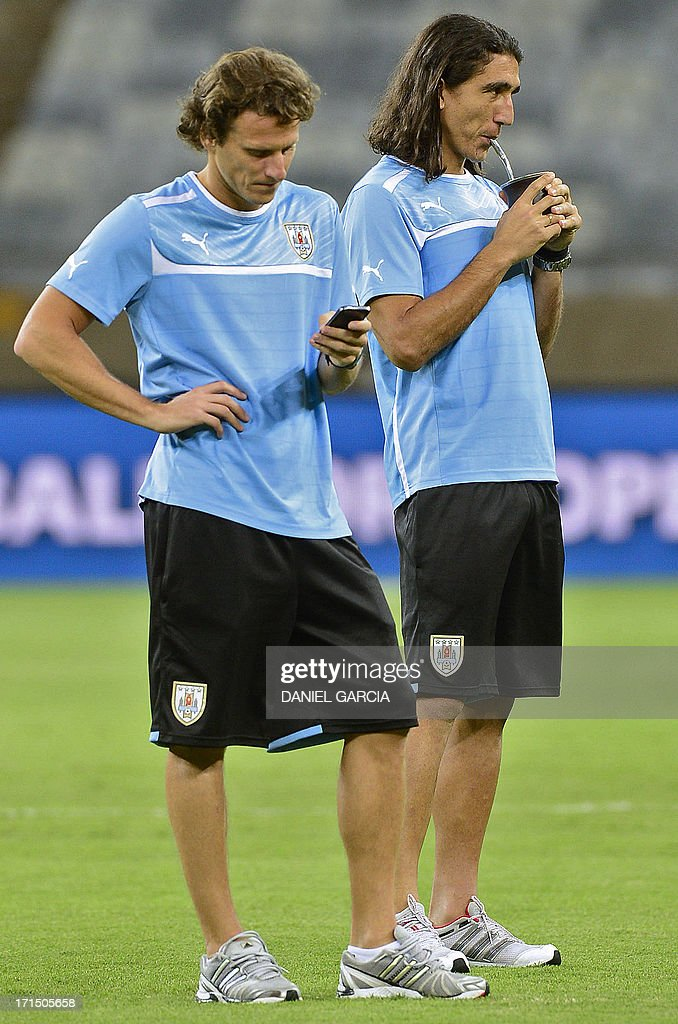 Uruguay's forward Diego Forlan checks his mobile phone as Uruguay's goalkeeper Juan Castillo sips mate (an herbal infusion) as the team makes the reconnaissance of the Mineirao Stadium in Belo Horizonte on the eve of their FIFA Confederations Cup Brazil 2013 semifinal match against Brazil.