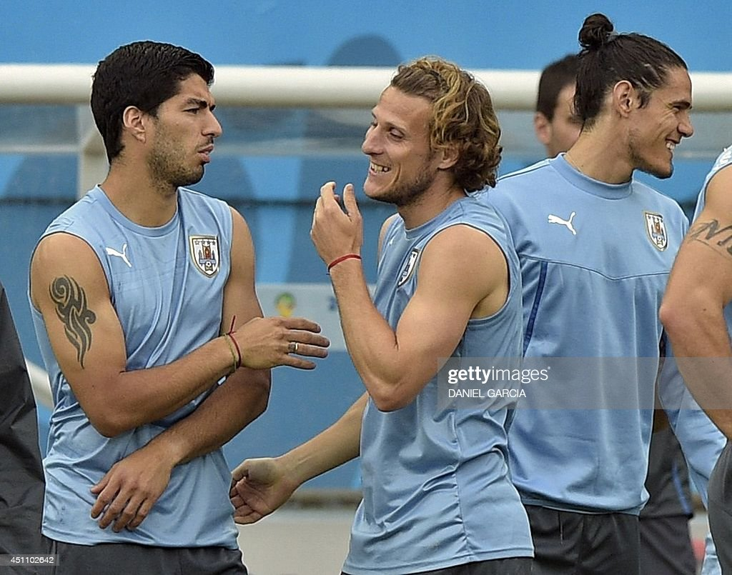 Uruguay s forward Diego Forlan C jokes with forward Luis Suarez