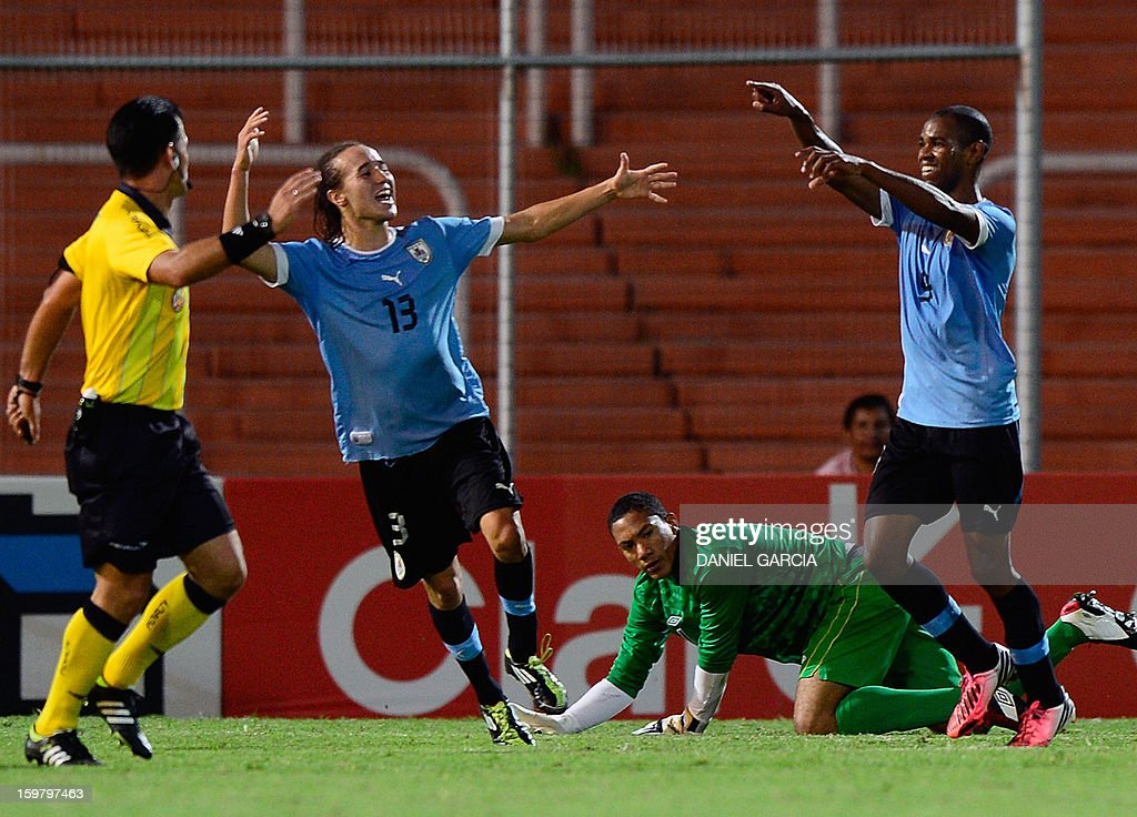 Uruguay's forward Diego Rolan (R) celebrates with teammate midfielder Diego Laxalt Suarez after scoring the third goal in front of Peru's goalkeeper Andy Vidal and Ecuadorean referee Carlos Vera (L) during their South American U-20 final round football match at Malvinas Argentinas stadium in Mendoza, Argentina, on January 20, 2013. Uruguay won by 3-1. Four teams will qualify for the FIFA U-20 World Cup Turkey 2013.