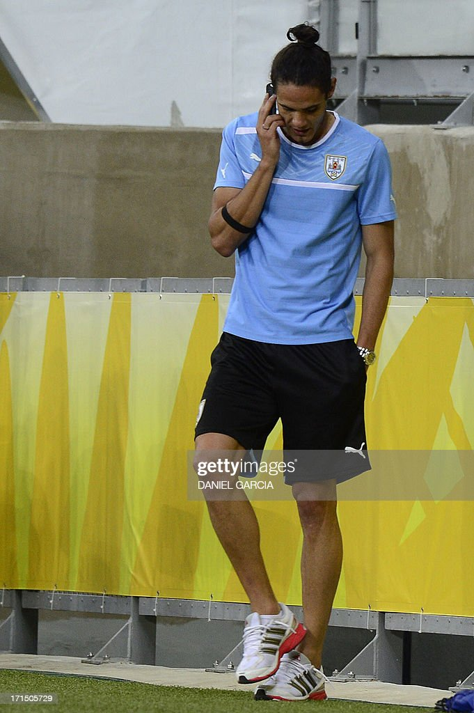 Uruguay's forward Edinson Cavani talks on a mobile phone as the team makes the reconnaissance of the Mineirao Stadium in Belo Horizonte on the eve of their FIFA Confederations Cup Brazil 2013 semifinal match against Brazil. AFP PHOTO / DANIEL GARCIA