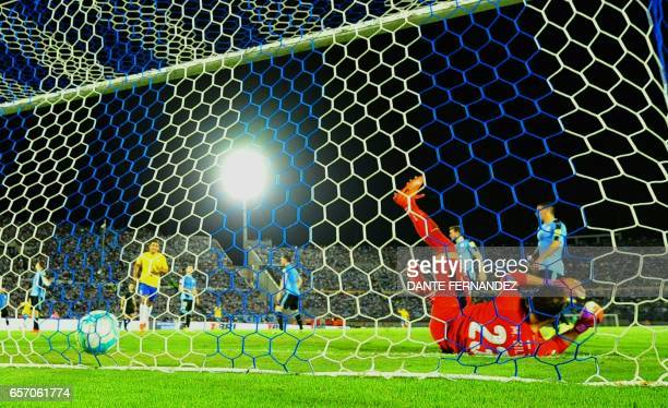 Uruguay's goalkeeper Martin Silva fails to stop a goal during their 2018 FIFA World Cup qualifier football match against Brazil at the Centenario...