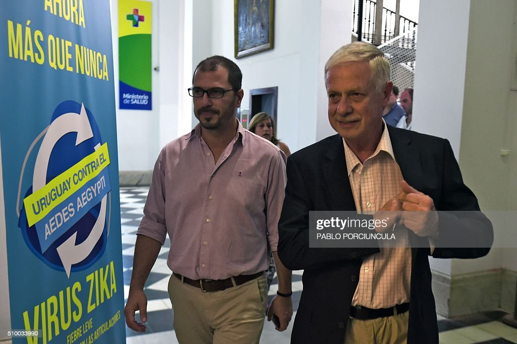 Uruguay's Health Minister Jorge Basso (R), accompanied by the Uruguayan president's assistant secretary Juan Andres Roballo, walk to a press conference to announce the first case of dengue fever detected in this country, in Montevideo on February 13, 2016. AFP PHOTO / PABLO PORCIUNCULA / AFP / PABLO PORCIUNCULA