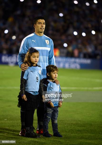 Uruguay's Luis Suarez sings the national anthem next to his children Delfina and Benjamin before the start of the 2018 World Cup football qualifier...