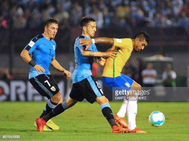 Uruguay's Matias Vecino and Cristian Rodriguez vie for the ball with Brazil's Paulinho during their 2018 FIFA World Cup qualifier football match at...