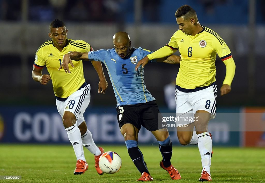 Uruguay's midfielder Carlos Sanchez (C) is marked by Colombia's Frank Fabra (L) and Edwin Cardona during their Russia 2018 FIFA World Cup South American Qualifiers football match, at the Estadio Centenario stadium in Montevideo, on October 13, 2015.
