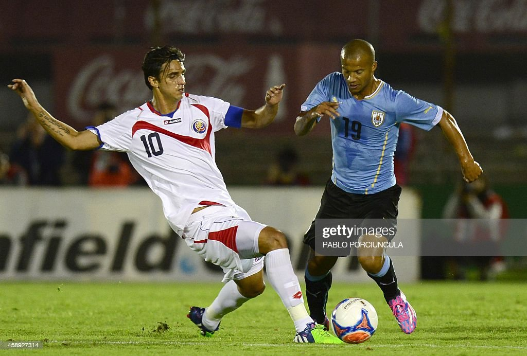 Uruguay's midfielder Carlos Sanchez (R) vies for the ball with Costa Rica's forward Braian Ruiz during a friendly football match at the Centenario stadium in Montevideo on November 13, 2014. AFP PHOTO / Pablo PORCIUNCULA