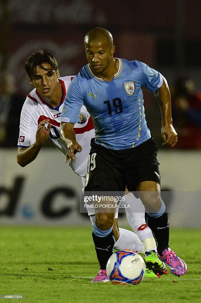 Uruguay's midfielder Carlos Sanchez (R) vies for the ball with Costa Rica's forward Braian Ruiz during a friendly football match at Centenario stadium in Montevideo on November 13, 2014. AFP PHOTO / Pablo PORCIUNCULA