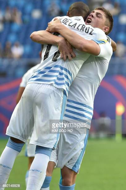 Uruguay's midfielder Federico Valverde is hugged by teammate Nicolas De La Cruz celebrates scoring during their U20 World Cup quarterfinal football...