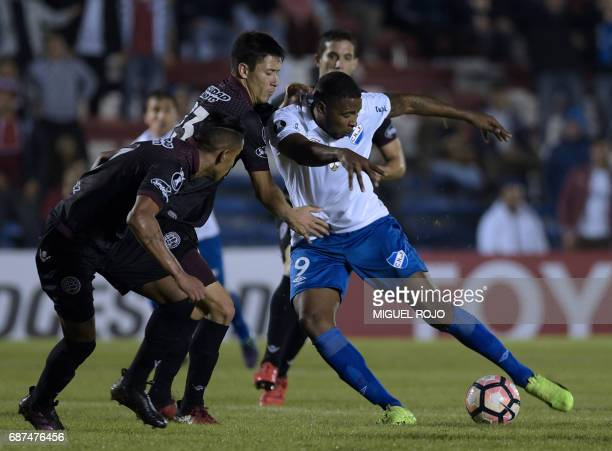Uruguay's Nacional Hugo Silveira is marked by Argentina's Lanus Jose Luis Gomez and Rolando Garcia during their Libertadores Cup football match at...