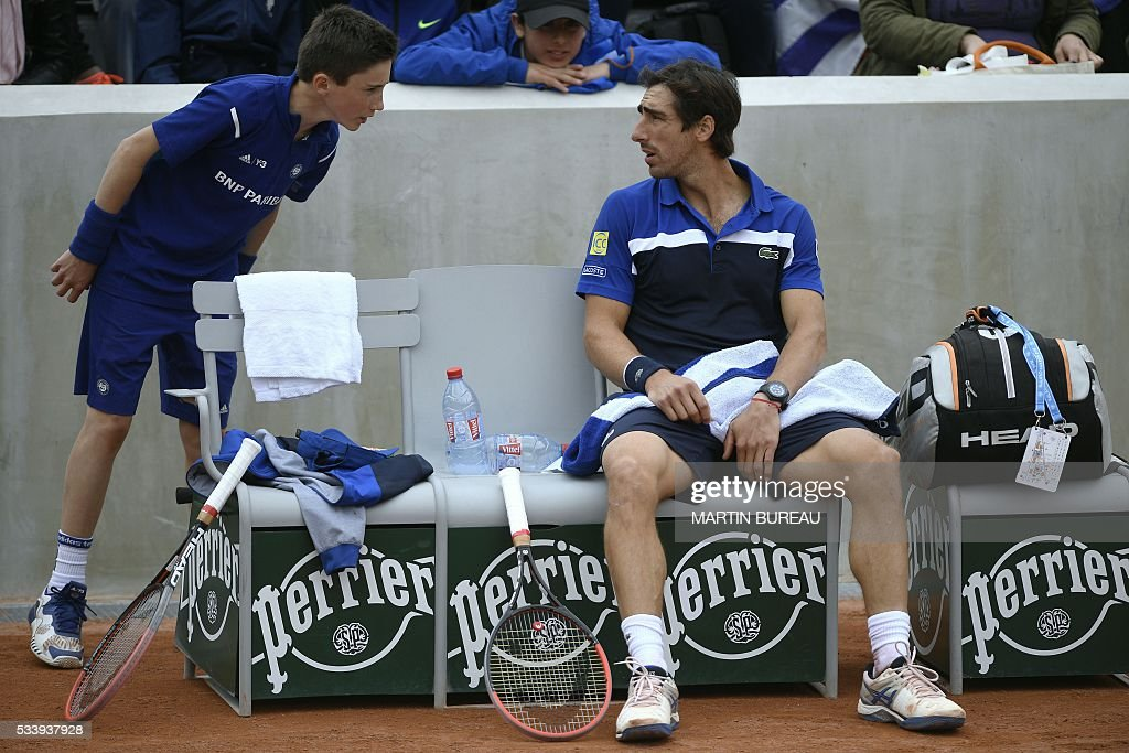 Uruguay's Pablo Cuevas speaks to a ball boy during his men's first round match against Germany's Tobias Kamke at the Roland Garros 2016 French Tennis Open in Paris on May 24, 2016. / AFP / MARTIN