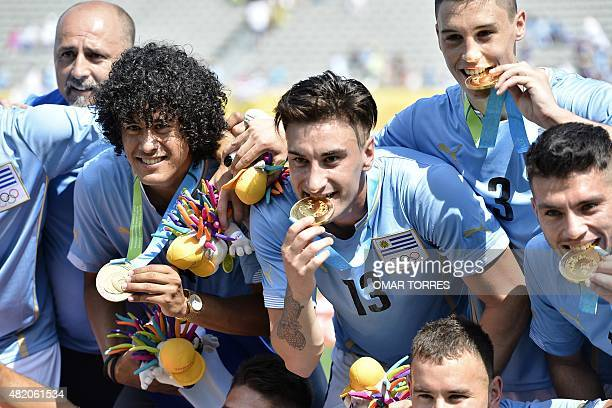 Uruguay's Paolo Lemos Erick Cabaco and Federico Ricca pose for pictures after receiving the gold medal after defeating Mexico in the final of the Pan...