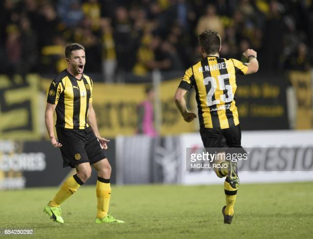 Uruguay's Penarol Lucas Hernandez celebrates with teammate Nahitan Nandez after scoring against Argentina's Atletico Tucuman during their...