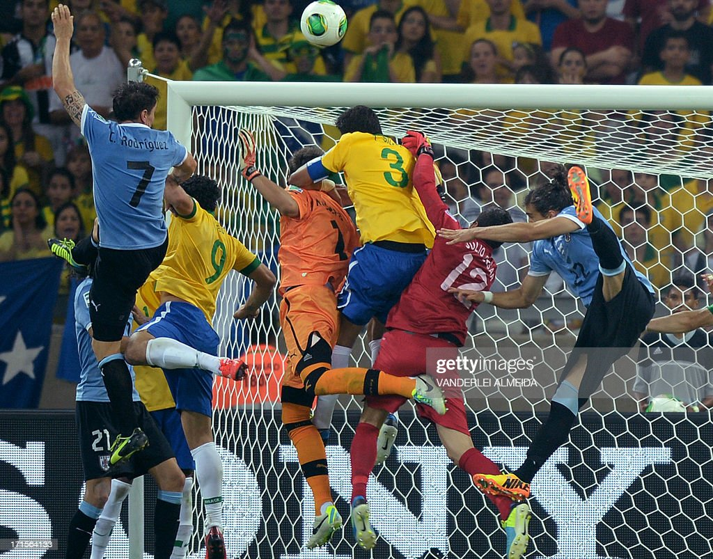 Uruguay's players (light blue and black) try to score past Brazil's goalkeeper Julio Cesar (in red) during their FIFA Confederations Cup Brazil 2013 semifinal football match against Brazil, at the Mineirao Stadium in Belo Horizonte on June 26, 2013.