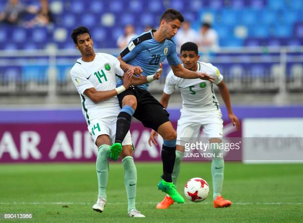 Uruguay's Rodrigo Bentancur fights for the ball with Saudi Arabia's Ali Alasmari and Abdulelah Alamri during their U20 World Cup round of 16 football...