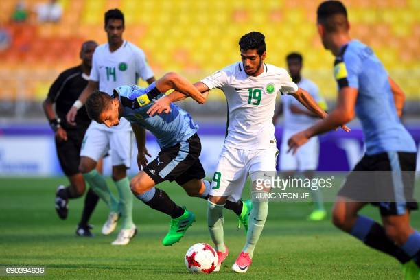 Uruguay's Rodrigo Bentancur fights for the ball with Saudi Arabia's Fahad Alrashidi during their U20 World Cup round of 16 football match between...