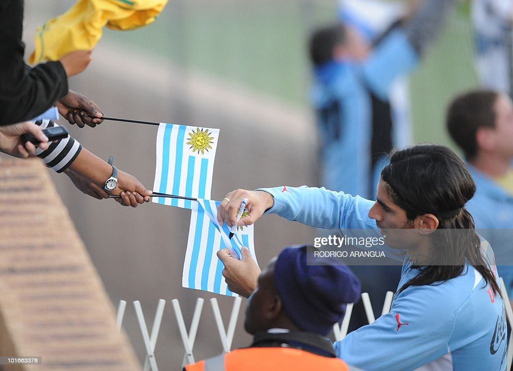 Uruguay's striker Sebastian Abreu sign autographs for local fans after a training sesion of the Uruguayan national team in Kimberley on June 6, 2010. Uruguay will play their first match of the 2010 World Cup against France on June 11 in Cape Town. AFP PHOTO / Rodrigo ARANGUA