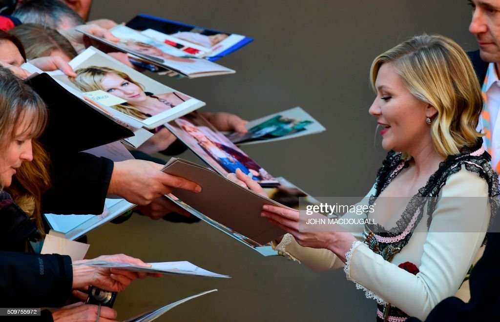 Us actress Kirsten Dunst signs autographs as she arrives for a photo call for the film ' Midnight Special by Jeff Nichols' screened in competition of the 66th Berlinale Film Festival in Berlin on February 12, 2016. / AFP / John MACDOUGALL