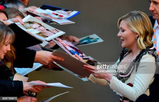 TOPSHOT Us actress Kirsten Dunst signs autographs as she arrives for a photo call for the film ' Midnight Special by Jeff Nichols' screened in...