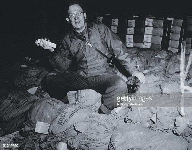 A Us Soldier Inspects Bags Of Money And Gold Taken From Jews By The Nazi's And Stored In The Heilbron Salt Mines May 3 1945