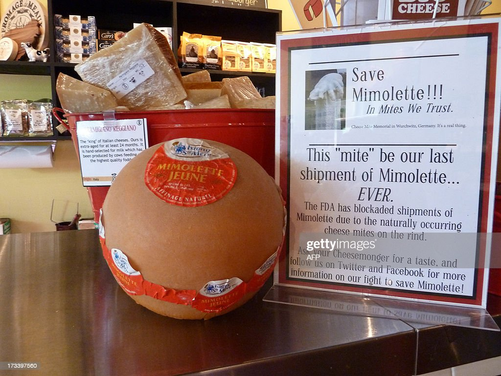 France-cheese-food-health-distribution A sign reads 'Save Mimolette!!!' at Cheestique in Arlington, Virginia, on July 11, 2013. Jill Erber, the owner of Cheestique, is campaigning against the US Food and Drug Administration (FDA) regulations that have blocked mimolette shipments from France to the US this spring due to naturally occuring mites in the rind of the cheese. AFP PHOTO/Fabienne FAUR