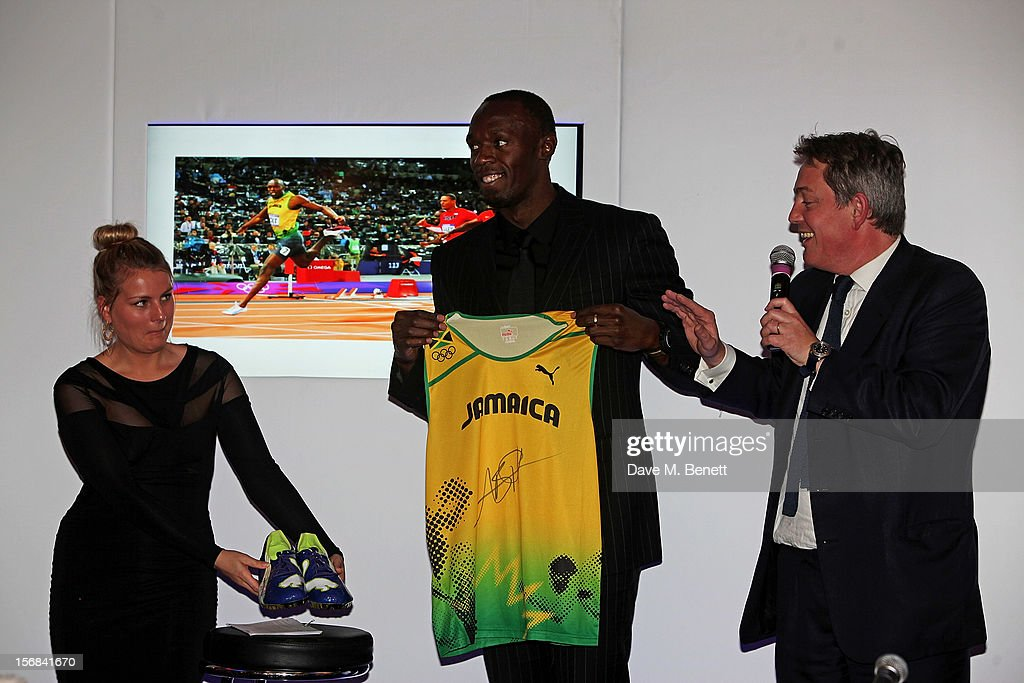 Usain Bolt (C) and auctioneer James Bruce-Gardyne attend the Zeitz Foundation and ZSL Gala at London Zoo on November 22, 2012 in London, England.