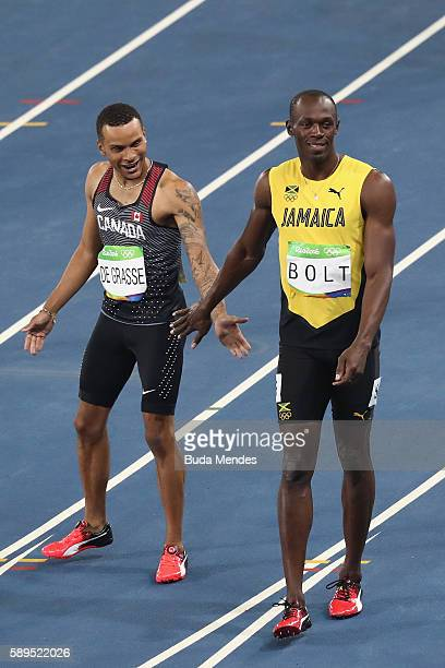 Usain Bolt of Jamaica and Andre De Grasse of Canada react after the Men's 100 meter semifinal on Day 9 of the Rio 2016 Olympic Games at the Olympic...