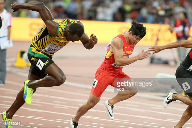 Usain Bolt of Jamaica and Bingtian Su of China compete in the Men's 100 metres semifinal during day two of the 15th IAAF World Athletics...
