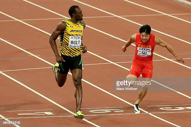 Usain Bolt of Jamaica and Bingtian Su of China cross the finish line in the Men's 100 metres semifinal during day two of the 15th IAAF World...