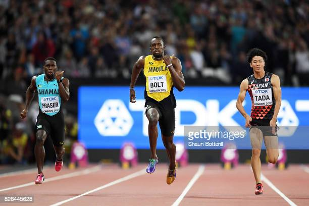 Usain Bolt of Jamaica and Shuhei Tada of Japan compete in the Men's 100 metres heats during day one of the 16th IAAF World Athletics Championships...