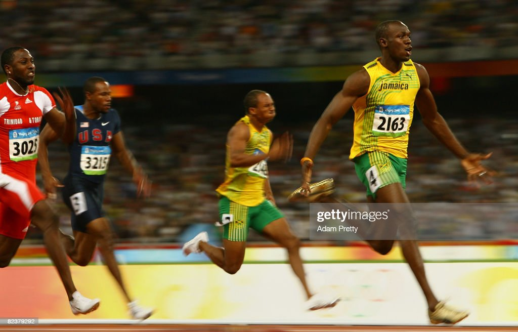 Usain Bolt of Jamaica (R) celebrates as he approaches the line on his way to winning the Men's 100m Final at the National Stadium on Day 8 of the Beijing 2008 Olympic Games on August 16, 2008 in Beijing, China. Bolt clocked a new world record time of 9.69 seconds.