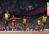 Usain Bolt of Jamaica celebrates as he crosses the finish line ahead of Wallace Spearmon of the United States Churandy Martina of Netherlands Yohan...
