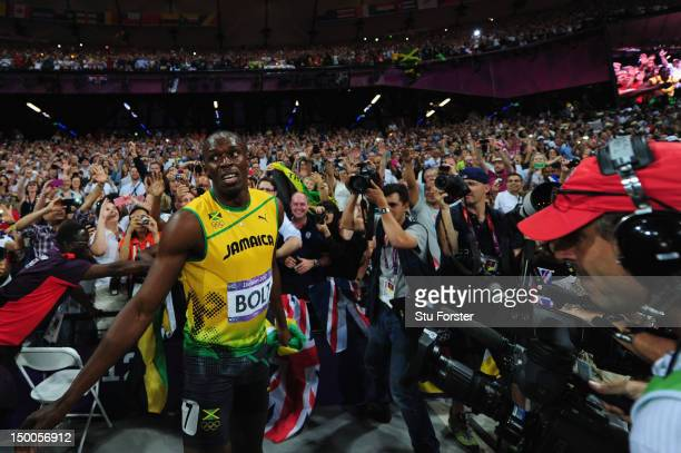 Usain Bolt of Jamaica celebrates in front of the crowd after winning gold in the Men's 200m Final on Day 13 of the London 2012 Olympic Games at...