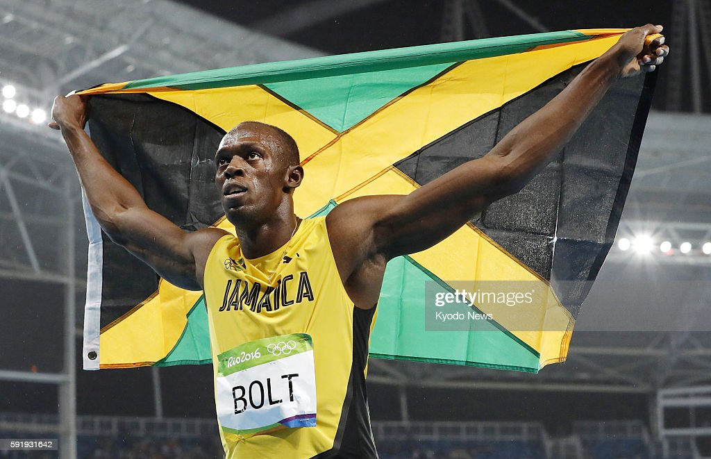 Usain Bolt of Jamaica celebrates with his country's national flag after winning the men's 200meter gold medal in the athletics competitions of the...