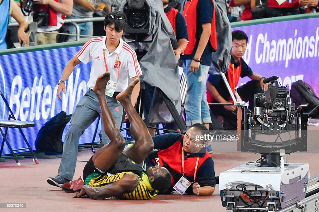 Usain Bolt of Jamaica collides with a worker as he celebrates after crossing the finish line to win gold in the Men's 200 metres final during day six of the 15th IAAF World Athletics Championships Beijing 2015 at Beijing National Stadium on August 27, 2015 in Beijing, China.