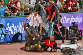 Usain Bolt of Jamaica collides with a worker as he celebrates after winning gold in the Men's 200 metres final during day six of the 15th IAAF World...