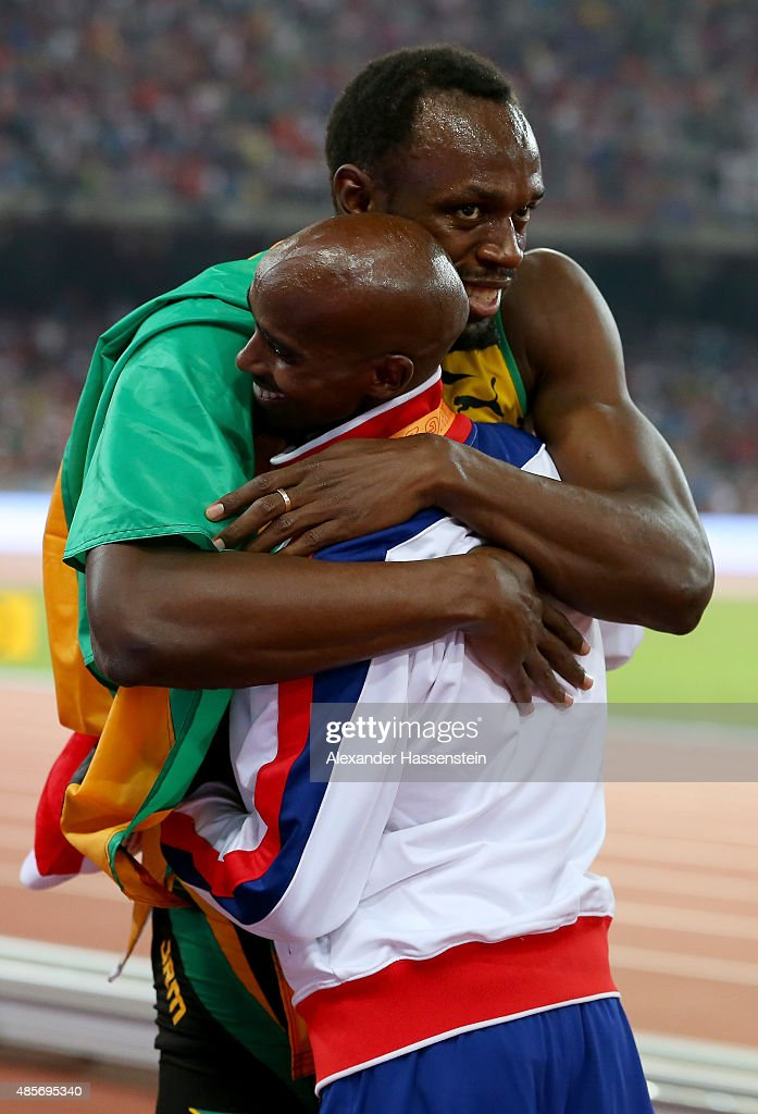 Usain Bolt of Jamaica congratulates gold medalist Mohamed Farah of Great Britain on the podium during the medal ceremony for the Men's 5000 metres final during day eight of the 15th IAAF World Athletics Championships Beijing 2015 at Beijing National Stadium on August 29, 2015 in Beijing, China.