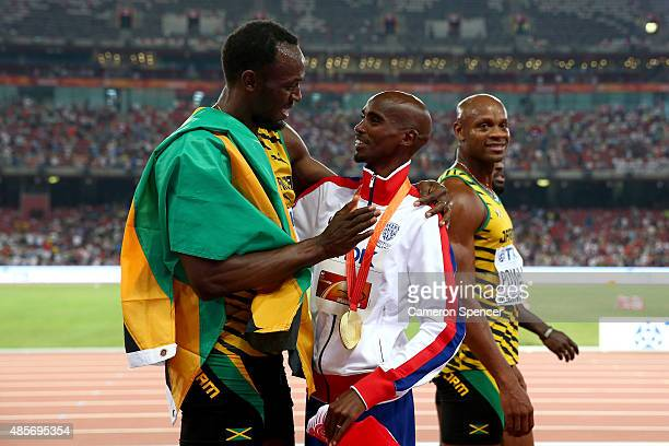 Usain Bolt of Jamaica congratulates gold medalist Mohamed Farah of Great Britain on the podium during the medal ceremony for the Men's 5000 metres...