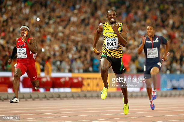 Usain Bolt of Jamaica crosses the finish line to win gold in the Men's 4x100 Metres Relay final ahead of Mike Rodgers of the United States during day...