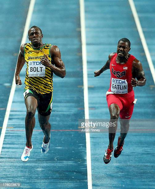Usain Bolt of Jamaica crosses the line to win gold ahead of Justin Gatlin of the United States in the Men's 100 metres Final during Day Two of the...