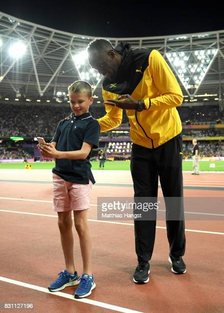 Usain Bolt of Jamaica greets a young fan as he bids farewell after his last World Athletics Championships during day ten of the 16th IAAF World...